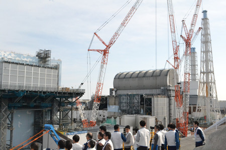 東京電力福島第1原発構内の高台から取材する報道陣。左側が2号機、丸い屋根が3号機=1月30日午後(代表撮影)