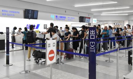 搭乗手続きで列をつくる福岡空港の利用客ら=14日午後、福岡市博多区