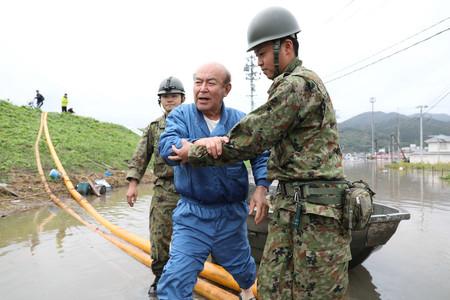 自衛隊員に救助される男性=14日午前、宮城県丸森町