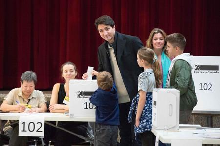 21日、モントリオールで、家族と共に投票するカナダのトルドー首相(中央)(AFP時事)