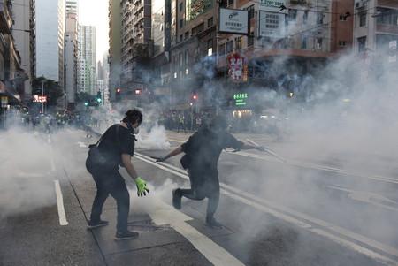 香港で警察が発射した催涙ガスが立ち込める中、抗議するデモ隊=2日(EPA時事)