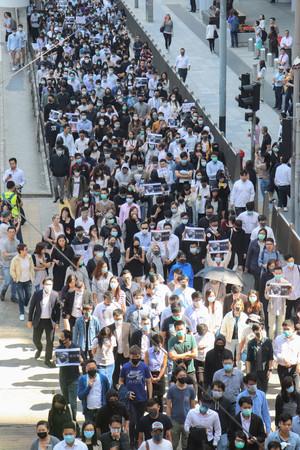 男子大学生が死亡したニュースを受け、オフィス街で抗議活動に参加する市民=8日午後、香港・香港島