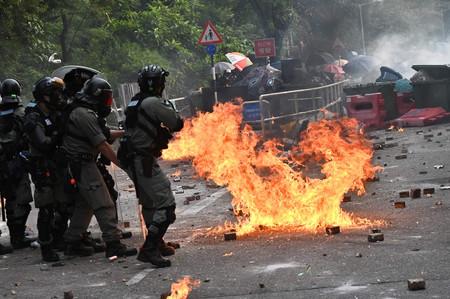 12日、香港の香港中文大で、デモ隊に催涙ガスを放つ警官隊(AFP時事)