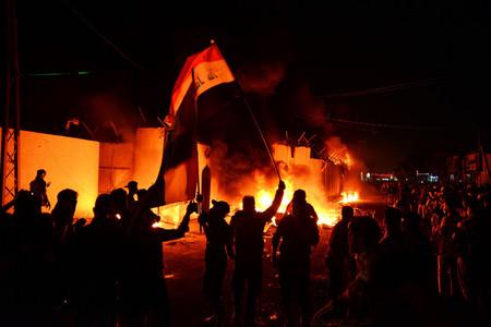 イラクのイスラム教シーア派聖地ナジャフで、燃え上がるイラン領事館前に集まるデモ隊=11月27日(AFP時事)