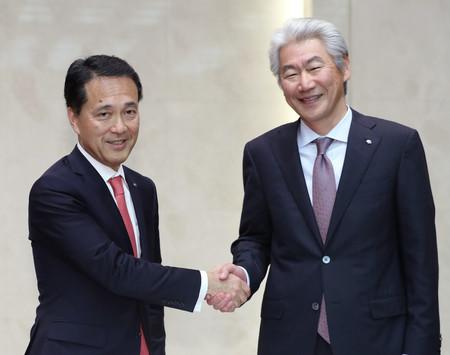記者会見で握手する野村ホールディングスの新CEOに就任する奥田健太郎・共同COO(左)と会長に退く永井浩二CEO=2日午後、東京都中央区