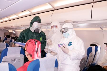 28日、浙江省舟山市の空港で、機内に乗り込み乗客の体温を測定する中国警察と医療班(EPA時事)