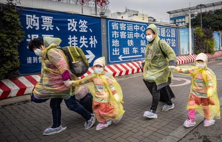 12日、中国・広州市の鉄道駅で新型コロナウイルスの感染を防ぐため体や足元を覆った乗客(EPA時事)