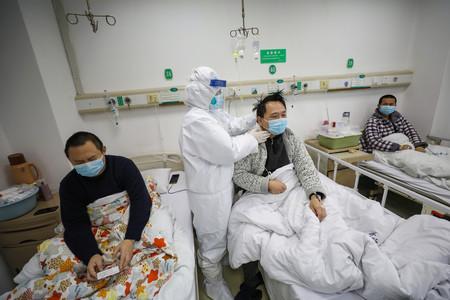 13日、中国湖北省武漢市の金銀潭病院で、患者の検診を行う医師(EPA時事)