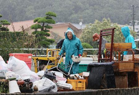 雨が強まる中、災害ごみを出す人たち。芦北町は災害廃棄物仮置き場がいっぱいになり、一時的に受け入れを停止している=9日午後、熊本県同町