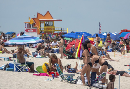 12日、新型コロナウイルスの感染が拡大する米南部フロリダ州マイアミビーチ市で海水浴を楽しむ人々(EPA時事)