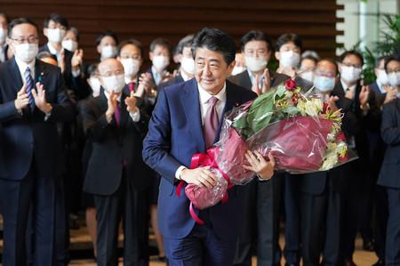 職員から花束を手渡され、首相官邸を出る安倍晋三首相=16日午後、東京・永田町