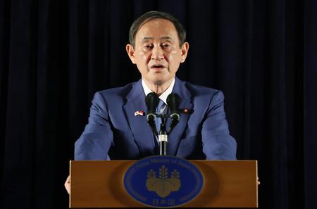 内外記者会見に臨む菅義偉首相=21日午前、ジャカルタ