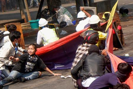 撃たれる直前、ミャンマー警察の発砲を受け他のデモ隊と一緒に地面に伏せるチェー・シンさん(手前左、黒いTシャツの女性)=3日、中部マンダレー(ロイター時事)