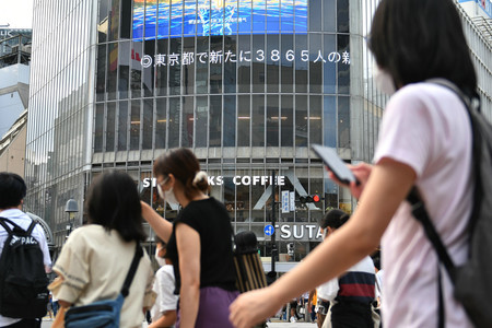 緊急事態宣言が発令される中、渋谷のスクランブル交差点を行き交う人々=29日、東京都渋谷区