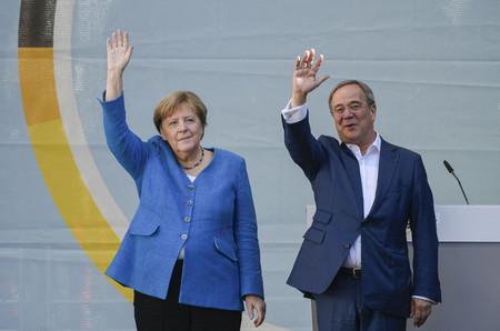 25日、ドイツ西部アーヘンで、支持者に手を振るメルケル首相(左)とキリスト教民主同盟(CDU)のラシェット党首(AFP時事)